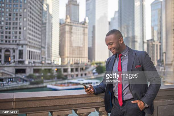 Businessman checking his mobile phone in downtown Chicago