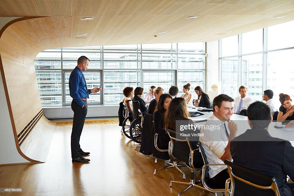 Businessman checking his phone at big meeting : Stock Photo
