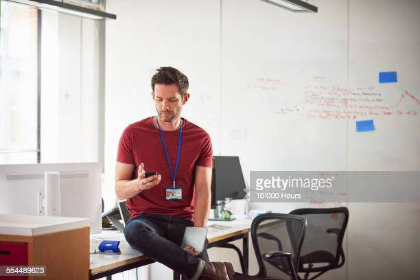 Businessman checking his phone in start-up office