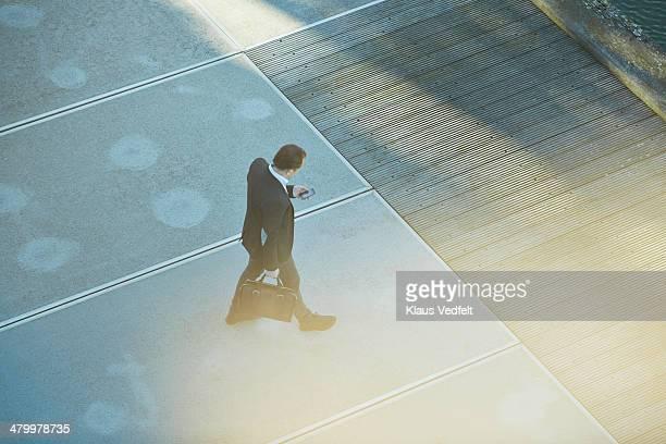 Businessman checking his phone while walking