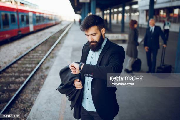 businessman checking his watch at train station - beat the clock stock photos and pictures