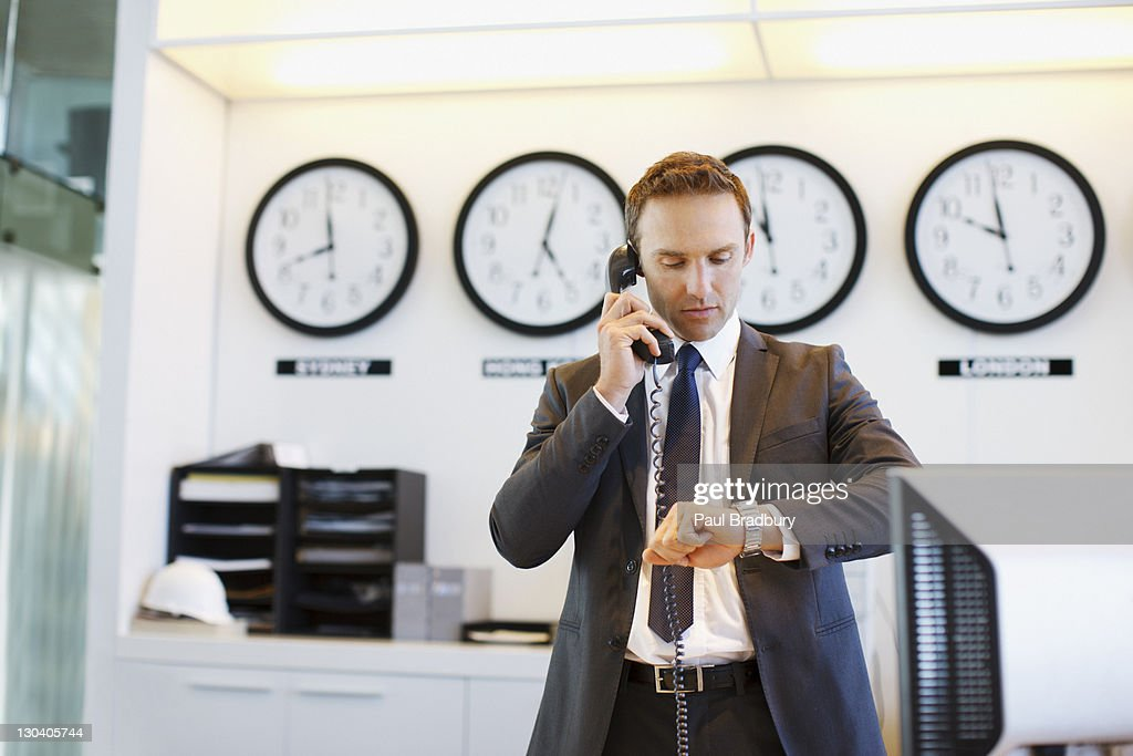 Businessman checking his watch in office : Stock Photo