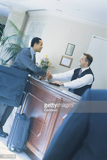 Businessman checking in at concierge desk
