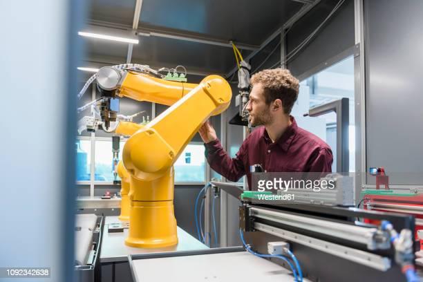businessman checking industrial robot in high tech company - automatisiert stock-fotos und bilder