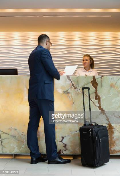businessman checking into hotel with concierge - road warrior stock photos and pictures