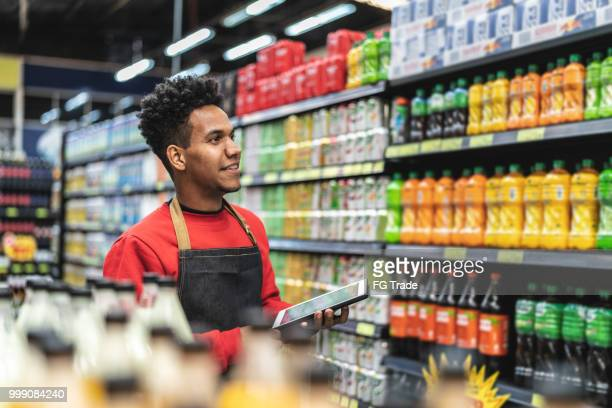 businessman checking inventory in a digital tablet at a supermarket - merchandise stock pictures, royalty-free photos & images