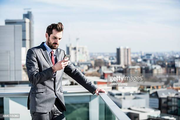 Businessman checking message over city
