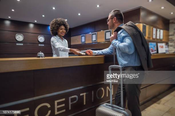 businessman checking out at the hotel reception desk - receptionist stock pictures, royalty-free photos & images