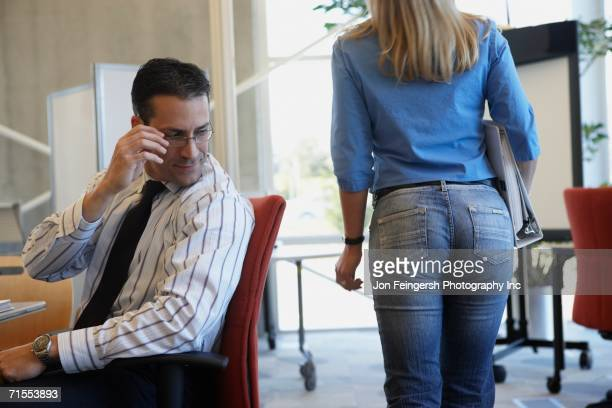businessman checking out female coworker - prejudice stock photos and pictures