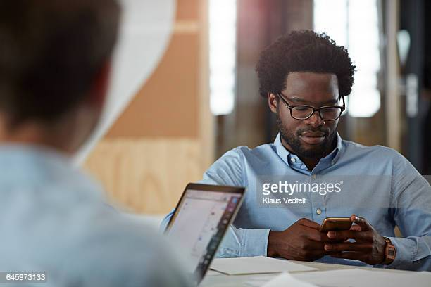 Businessman checking phone at office