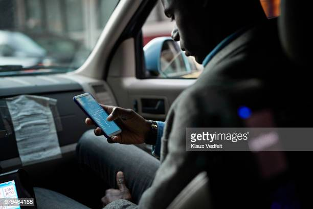 Businessman checking phone, while in a cab