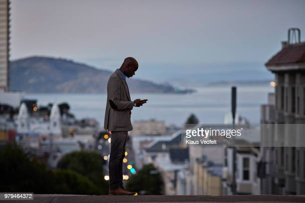 Businessman checking phone while on the street in the evening