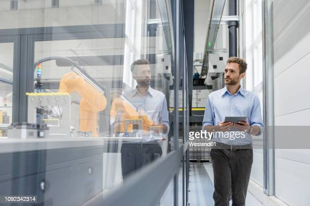 businessman checking robots with digital tablet in high tech company - industriebetrieb stock-fotos und bilder