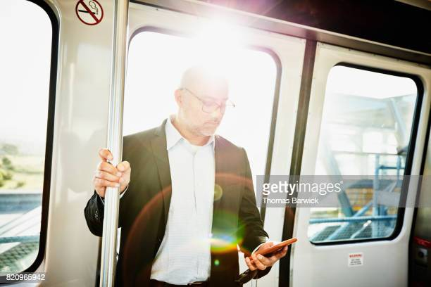 Businessman checking smartphone while riding on commuter train