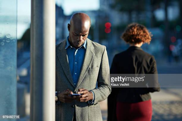 Businessman checking smartphone while waiting for the tram in San Francisco