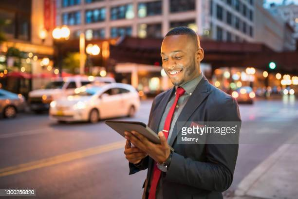 businessman checking social media messages on 5g digital tablet in chicago - mlenny stock pictures, royalty-free photos & images
