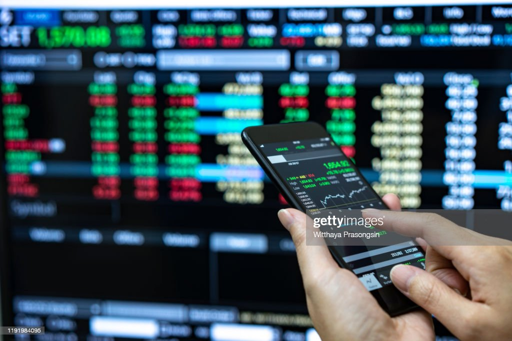 Businessman checking stock market data. He using a mobile phone. Analysis economy data on forex earn graph. : Stock-Foto