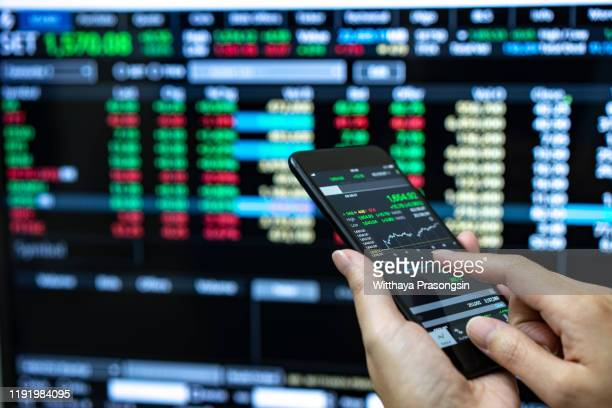 businessman checking stock market data. he using a mobile phone. analysis economy data on forex earn graph. - börse stock-fotos und bilder