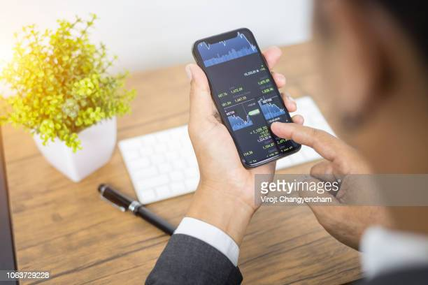 businessman checking stock market on mobile application - charity benefit fotografías e imágenes de stock