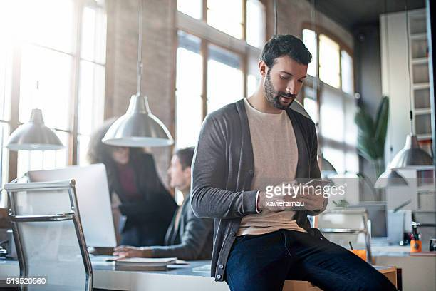businessman checking the mobile phone sitting on his desk - vaardigheid stockfoto's en -beelden