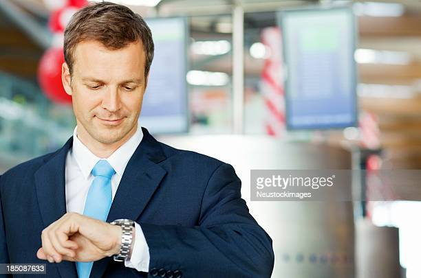 Businessman Checking The Time At Airport