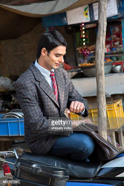Businessman checking the time on a motorcycle