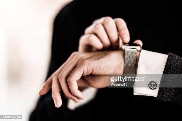 businessman checking the time on his smartwatch - 袖口 ストックフォトと画像