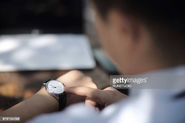 businessman checking the time on his watch - temps qui passe photos et images de collection