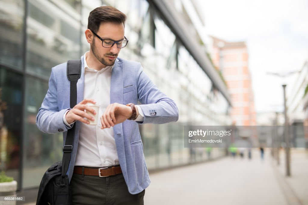 Empresário verificar o tempo em seu relógio de pulso : Foto de stock