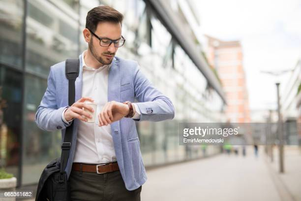 businessman checking the time on his wrist watch - instrument of time stock photos and pictures