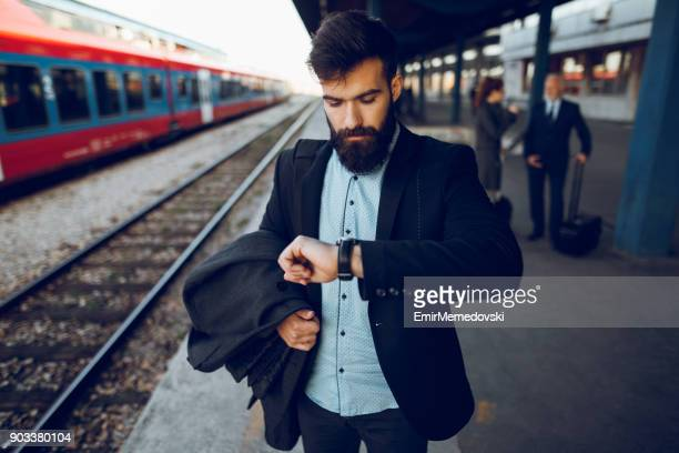 businessman checking the time on his wristwatch at train station - waiting stock pictures, royalty-free photos & images
