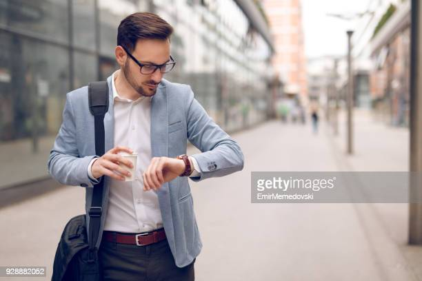 businessman checking the time on his wristwatch - shoulder bag stock pictures, royalty-free photos & images