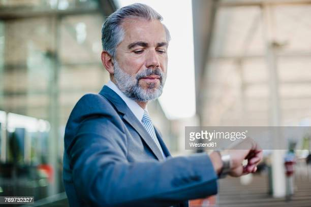businessman checking the time outdoors - time management stock photos and pictures