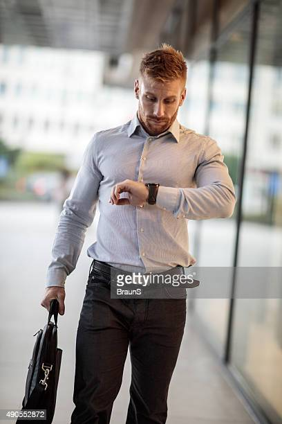 Businessman checking the time while going to work.