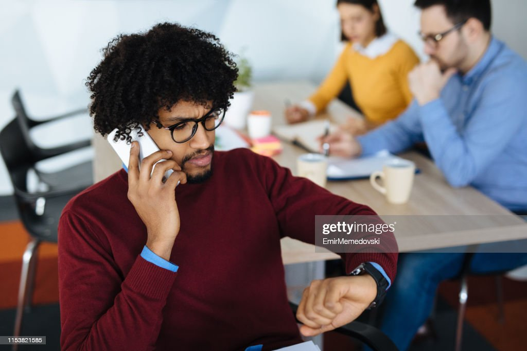 Businessman checking the time while talking on the phone : Stock Photo