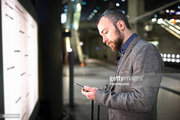 businessman checking the train time on the timetables