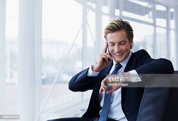 businessman checking time in office - formele zakelijke kleding stockfoto's en -beelden