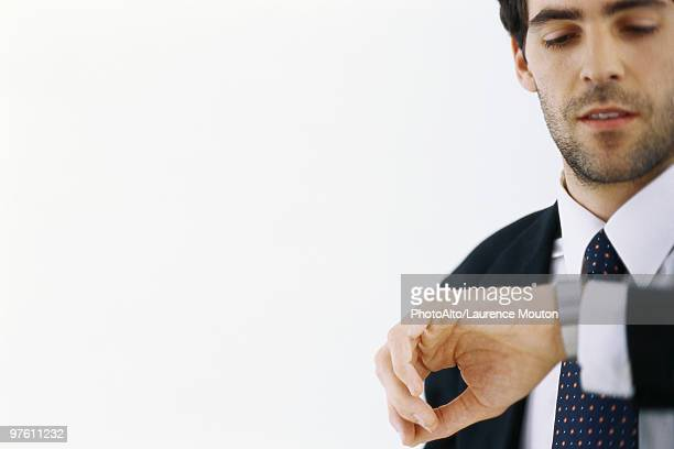 Businessman checking time, looking at watch