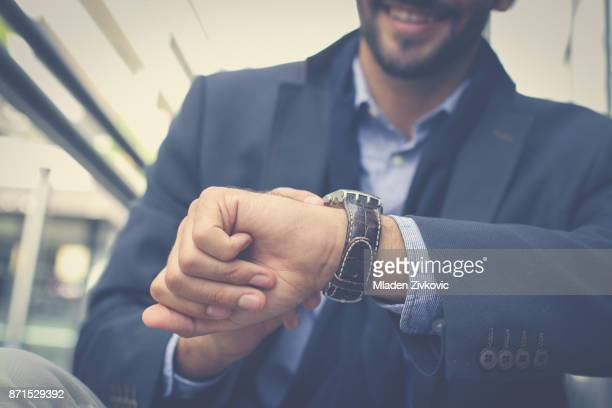 businessman checking time on watch. focus is on hand. - instrument of time stock photos and pictures