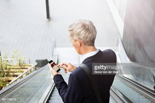 businessman checks phone, standing on escalator