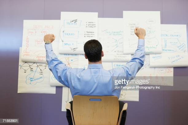 businessman cheering in front of wall charts - initiative stock pictures, royalty-free photos & images