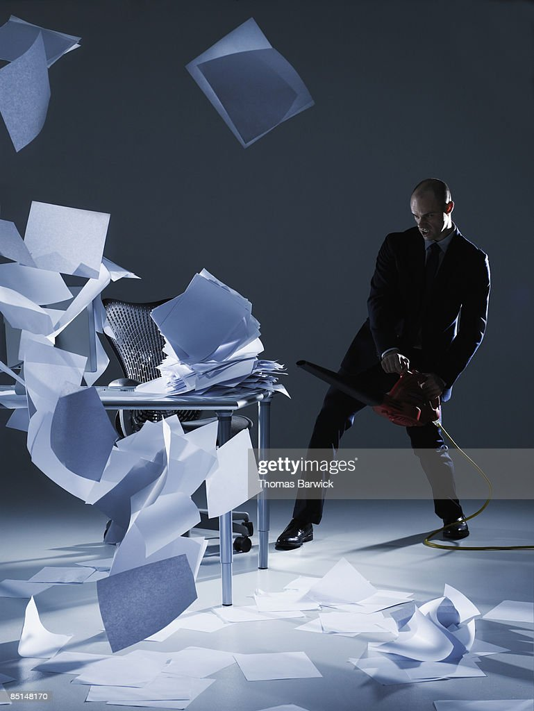 Businessman cleaning papers with leaf blower : Stock Photo