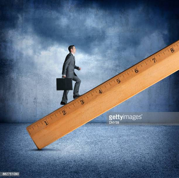 Businessman Climbing A Large Wooden Ruler