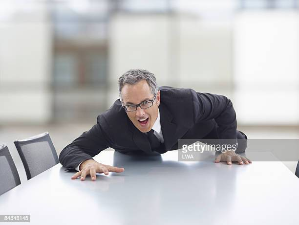 Businessman Climbing Across Conference Table