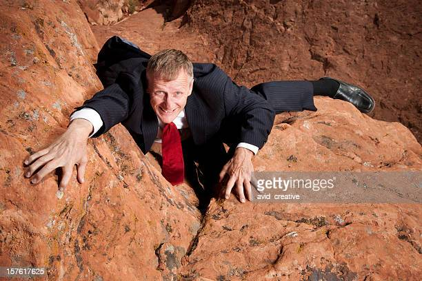Businessman Climbing Cliff