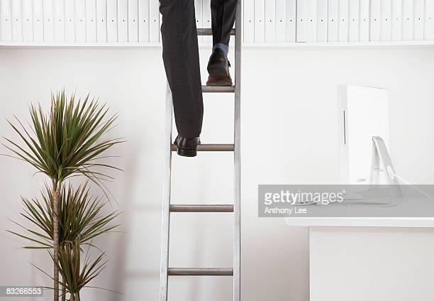 Businessman climbing ladder to reach binders