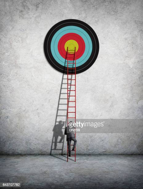 Businessman Climbing Ladder To Reach Target