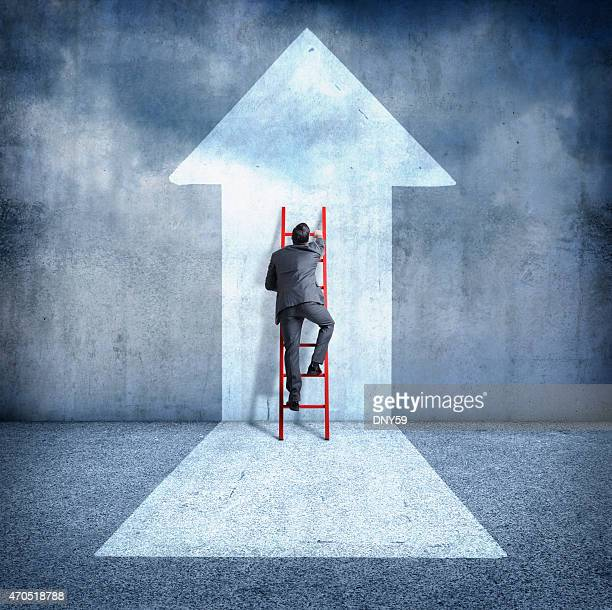 Businessman climbing ladder towards success