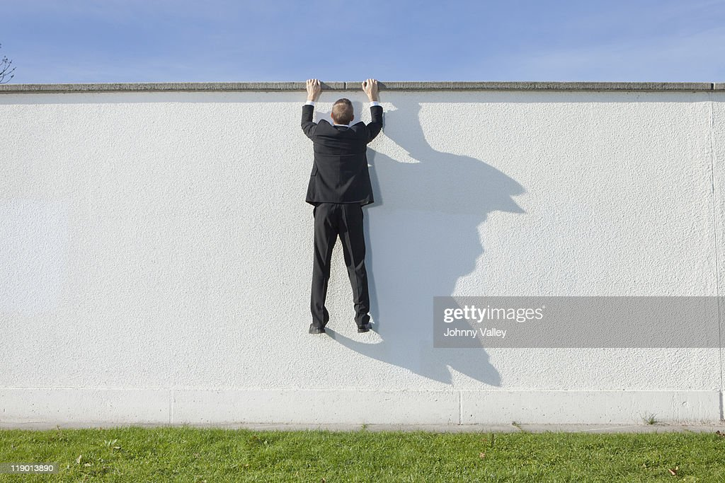 Businessman climbing over wall : Stock Photo