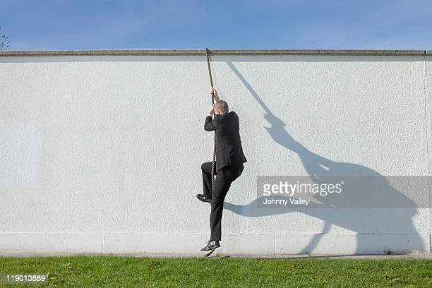 businessman climbing over wall with rope - initiative stock pictures, royalty-free photos & images